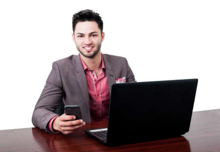 Dark hair business man smiling and sitting at his desk with a laptop in front and a smartphone in his hand photo