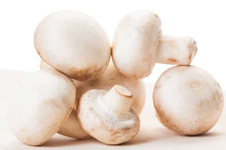 Closeup of bunch of champignon mushrooms on a wooden board and white background photo