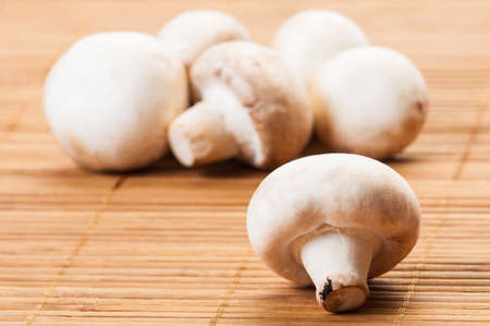 Bunch of champignon mushrooms on bamboo plate with focus on one photo