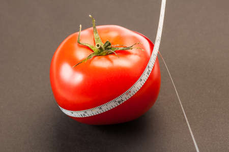coking: A diet using red tomatoes concept using a white thin centimeter to measure the calories. On a dark background