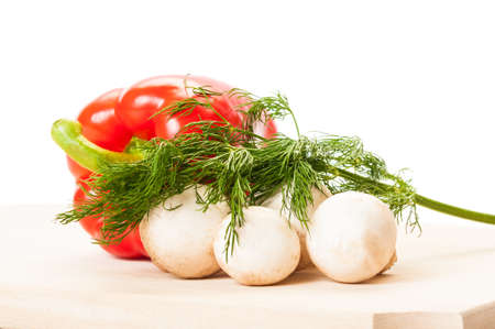 One red pepper a bunch of  champignon mushrooms and some green fresh dill on a wooden board and white background. photo