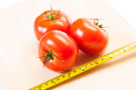 coking: Measure the calories of three red tomatoes for a diet, with a centimeter on a wooden board and white background Stock Photo