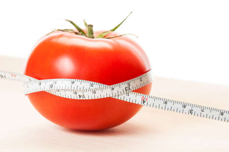 coking: Loose weight with perfect red tomatoes diet concept. Wooden board, red tomato, white centimeter and background.