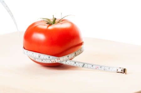 coking: Measure calories of a perfect red tomato with a centimeter. Diet concept made of tomato, meter, wooden board and white background.