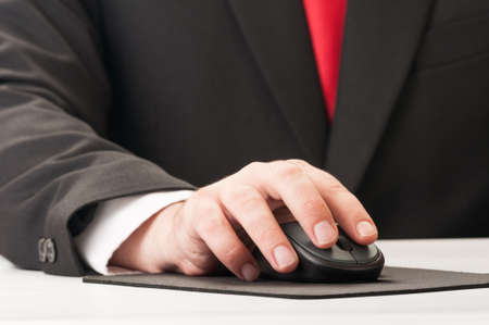 Closeup of hand and mouse, suit and tie. photo