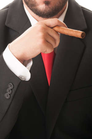 Elegant businessman smoking a cuban cigar. He wears a clasic black suit and red tie. photo
