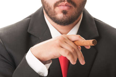 Young and elegant businessman smoking a cuban cigar. He wears a clasic black suit and red tie. photo