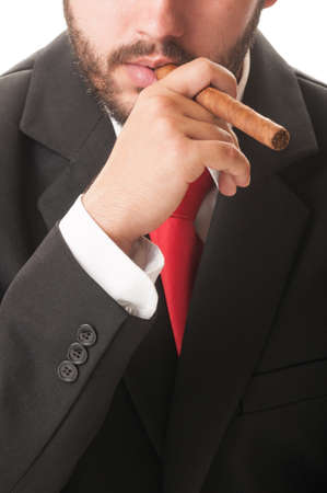 Sales agent smoking a cuban cigar. He wears a clasic black suit and red tie. photo