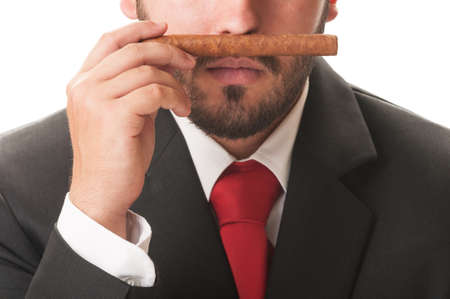 Business man smelling an original cuban cigar. He wears a clasic black suit and red tie. photo