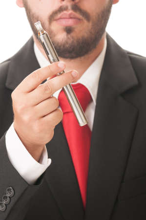 Business man holding an electronic cigarette. He wears clasic black suit and red tie. photo