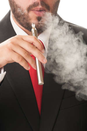 Business man smoking electronic cigarette or e-cig. He wears clasic black suit and red tie. photo