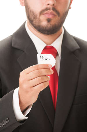 News concept using a man wearing a black suit and red necktie and holding a piece of paper with the word news on it. photo