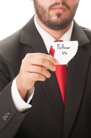 Follow us concept using a man wearing a black suit and red necktie and holding a piece of paper with the text follow us on it. photo