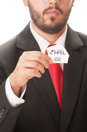 Email us concept using a man wearing a black suit and red necktie and holding a piece of paper with the text email us on it and a graphic envelope. photo