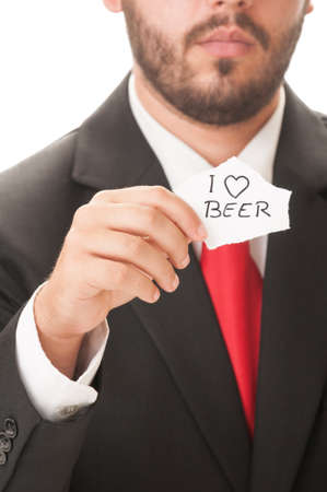 necktie beer: I love beer concept using a man wearing a black suit and red necktie and holding a piece of paper with the text I love beer on it. Stock Photo