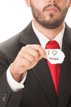 I love music concept using a man wearing a black suit and red necktie and holding a piece of paper with the text I love music on it. photo