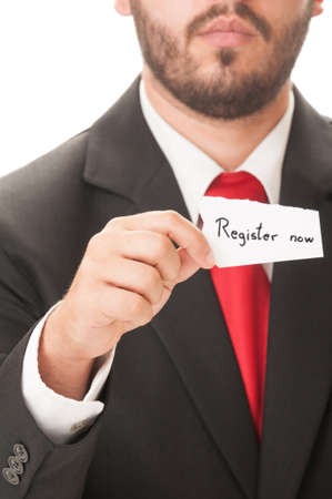 Register now concept using a man wearing a black suit and red necktie and holding a piece of paper with the text register now on it. photo