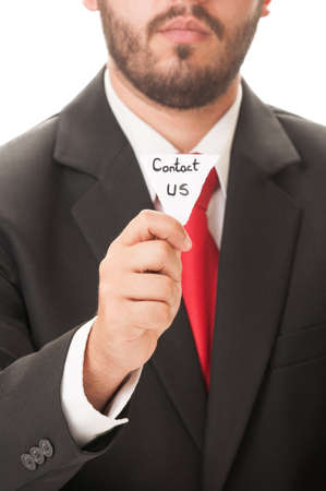 Contact us concept using a man wearing a black suit and red necktie and holding a piece of paper with the text contact us on it. photo
