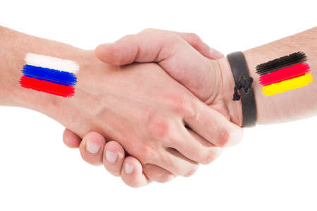 Russia and Germany hands shaking with flags painted on arms concept. Isolated on white background. photo