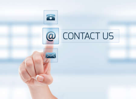 contact person: Female hand touching contact us button. Futuristic contact us concept on light blue Stock Photo