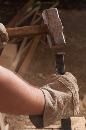 Worker hands using a hammer hitting a chisel photo