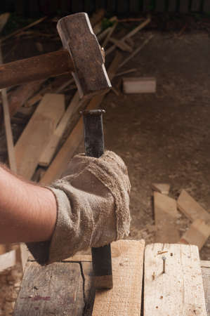 Carpenter at work using a hamer hitting a chisel photo