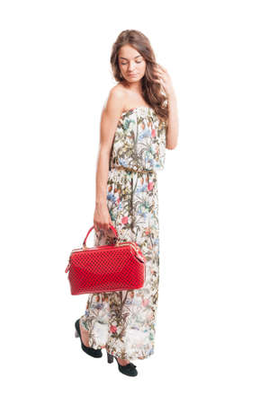 Beautiful long hair female model holding a red purse isolated on white studio background photo