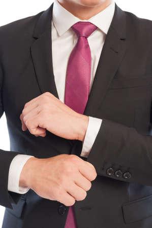 elegant business man: Ritratto di un elegante uomo d'affari, che fissa la manica della camicia da sotto la giacca