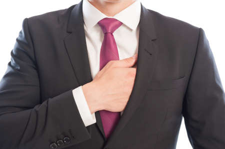 Elegant male model reaching his interior suit pocket with the right hand photo