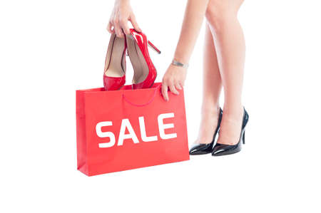 Woman shoes sale concept using red shopping bag and shoes isolated on white background photo
