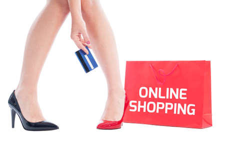 Online shopping using credit card concept using woman holding card and red shopping bag photo