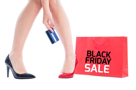 Online Black Friday sale concept using woman holding credit card and red shopping bag photo