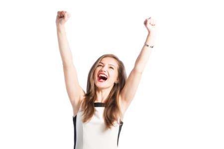 Portrait of a successful business woman raising arms up in the air and screaming for happiness photo