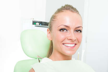 Portrait of a girl with perfect smile at dentist ready for oral treatment photo