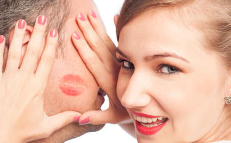 cheek to cheek: Beautiful woman framing lipstick kiss on a man face