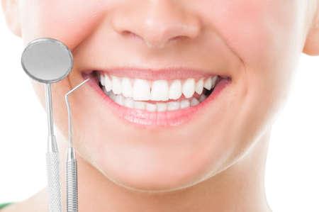 Primer plano de la sonrisa y el dentista herramientas perfectas en el fondo blanco Foto de archivo