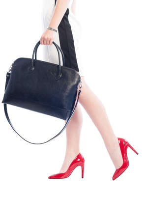 Business woman walking in red shoes with high heels and holding elegant black handbag isolated on white background Reklamní fotografie