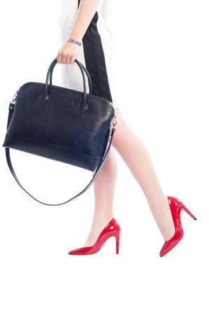 piernas con tacones: Mujer de negocios que recorre en zapatos rojos de tacón alto y sosteniendo elegante bolso negro aislado en fondo blanco