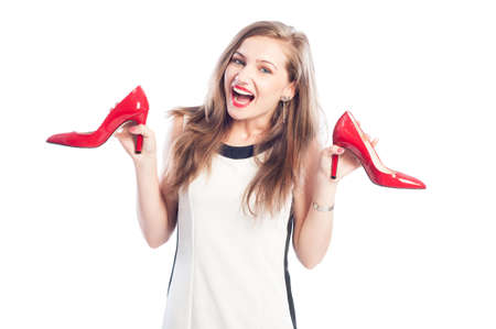 Excited woman holding new red shoes that she found on sale photo