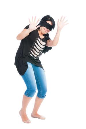 ojos vendados: Muchacha adolescente con los ojos vendados que act�a asustada y elevar las manos para defender y proteger a s� misma Foto de archivo