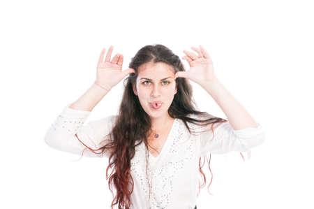 sacar la lengua: Chica joven que hace la cara usando divertidos manos y pegue la lengua Foto de archivo