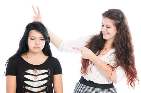 arrogant teen: Bully girl making rabbit ears. Bullying concept between girls isolated on white background Stock Photo