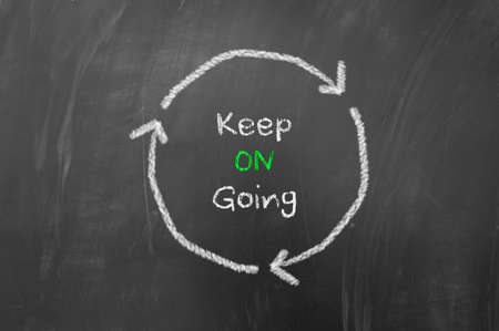 perseverance: Keep going concept using arrows in a circle on blackboard or chalk board Stock Photo