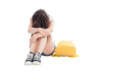 Upset girl holding her head on knees on white background