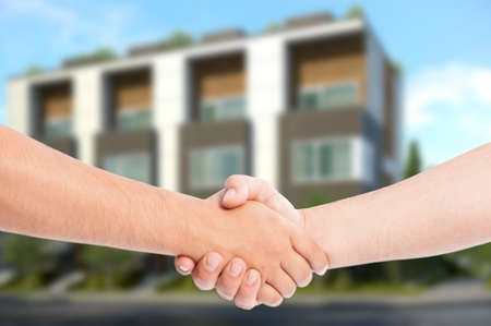 Real estate business concept with shaking hands and apartment building in the background photo