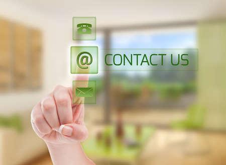 Contact Makelaar futuristische concept met behulp van een vrouw indrukken van een knop op transparant scherm met huis interieur als achtergrond Stockfoto