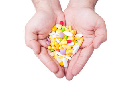 A man is holding a lot of different pills in both his hands