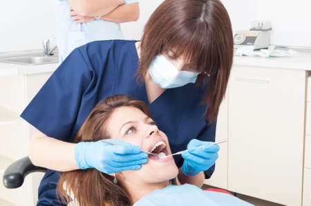 dental medicine: Oral hygienist or orthodontist at work on a female patient with beautiful teeth