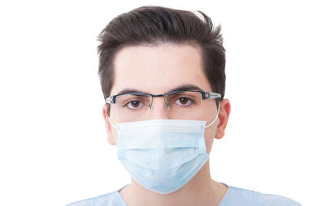 surgeon mask: Closeup with the face of a young doctor wearing medical or surgical mask