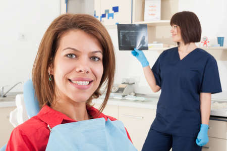 odontology: Female patient smiling and woman dentist doctor checking radiography in the background Stock Photo